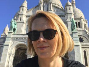 Laura mit Sonnenbrille vor einer Kirche